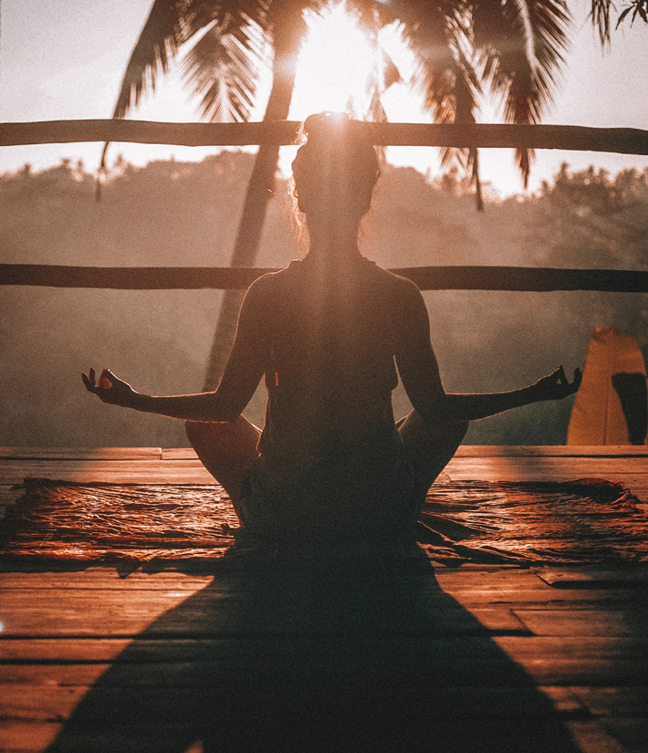 woman meditating at sunset while seated with her back facing the camera - how to be a powerful woman
