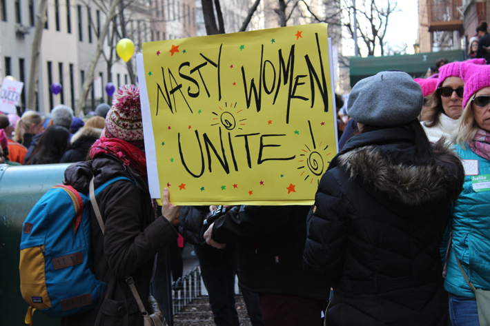 women protesting with a sign that reads nasty women unite - how to be a powerful woman