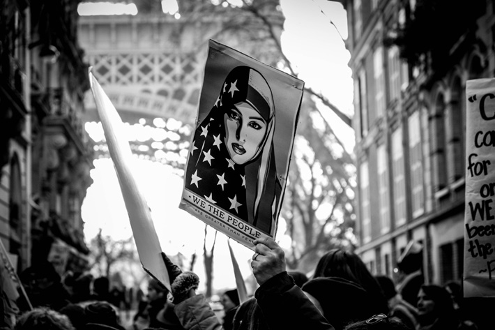 women empowerment march in paris with a we the people sign showing a woman wearing an american flag on her head and the eiffel tower in the background