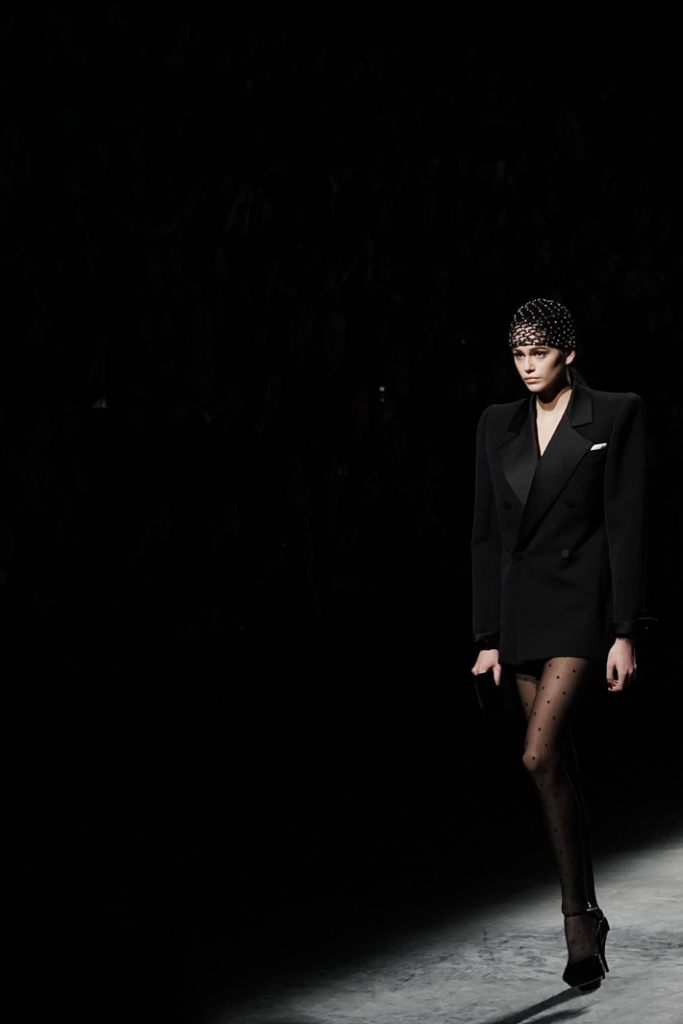 Model Kaia Gerber walks the runway in a black tuxedo blazer with polka dot tights during the Saint Laurent show as part of the Paris Fashion Week Fall/Winter 2019/2020 Womenswear presentation