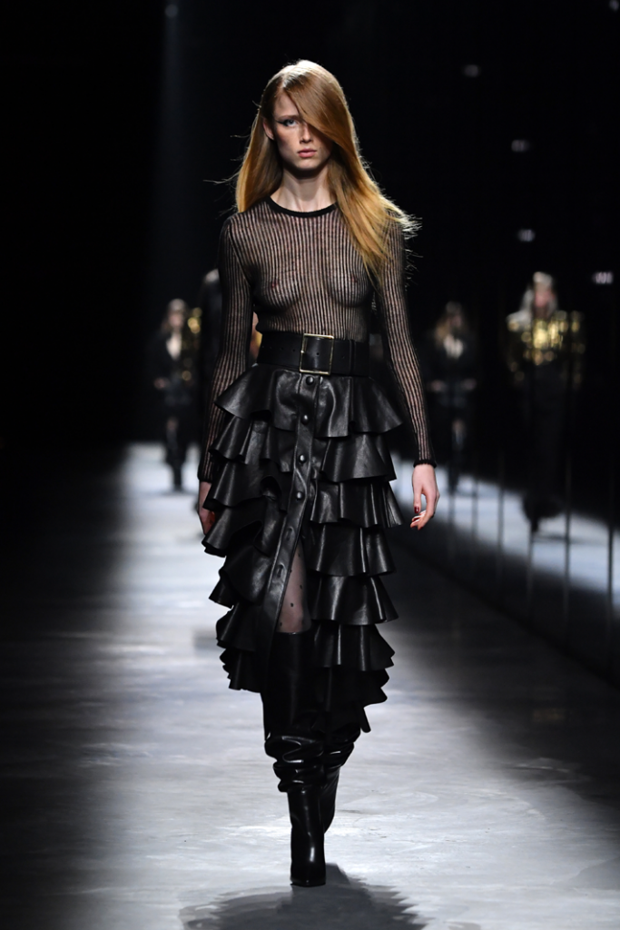 A model walks the runway with a see through shirt and black leather ruffled skirt during the Saint Laurent show at Paris Fashion Week Fall/Winter 2019/2020 Womenswear  presentation
