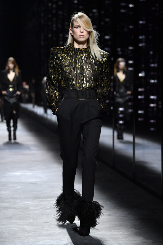 A model walks the runway during the Saint Laurent show in a black and gold animal print top, black pants and feathered booties at Paris Fashion Week Fall/Winter 2019/2020 Womenswear  presentation Source: Photo by Pascal Le Segretain/Getty Images