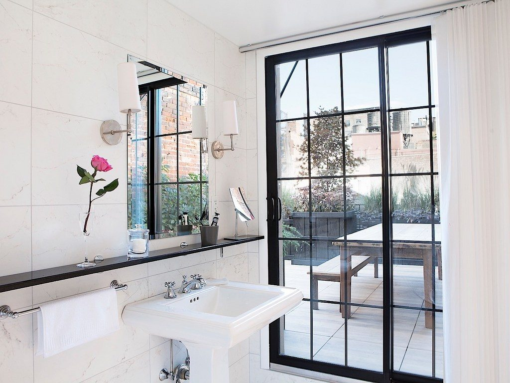 white bathroom overlooking a rooftop patio at the broome hotel new york - a top boutique hotel in nyc