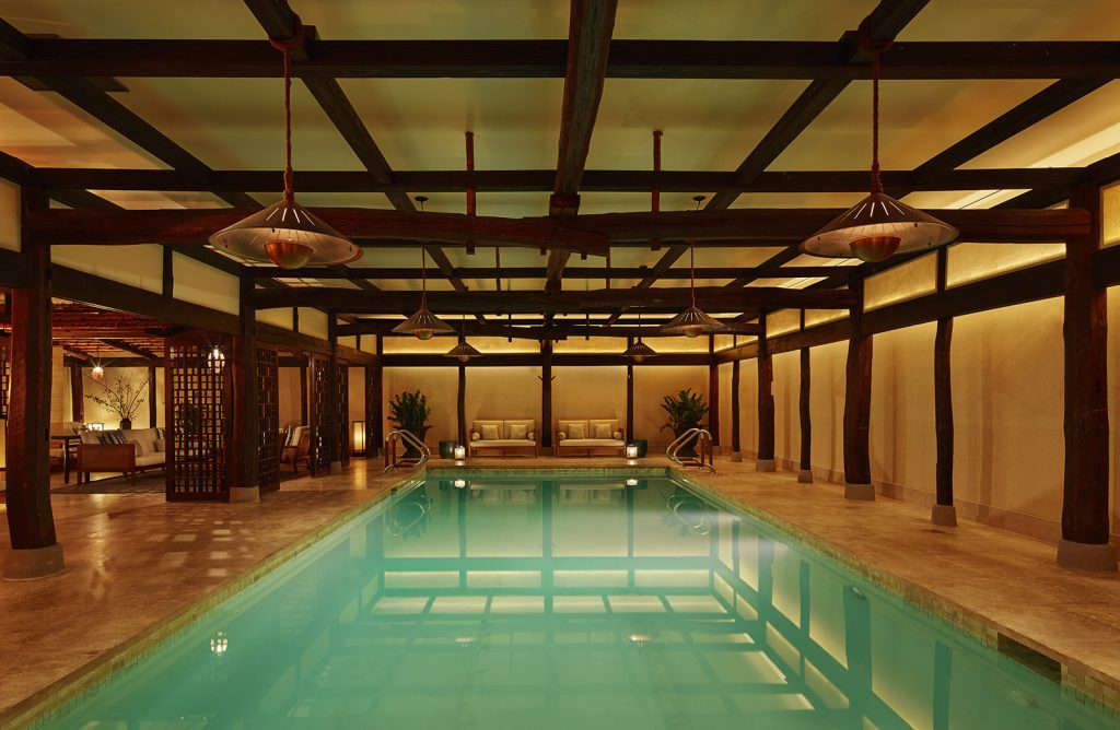 a pool lit by lanterns and enclosed in the walls of a Japanese farmhouse at the Greenwich Hotel in new york city - a top boutique hotel in nyc