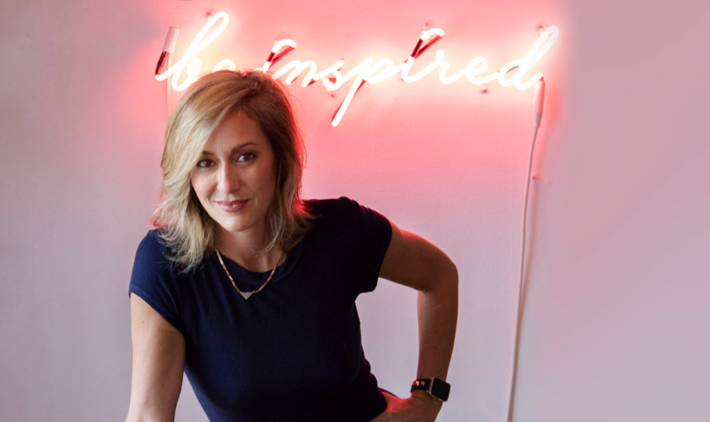 be inspired neon sign behind ginna christensen of GC collaborative - brand consultant for the design industry