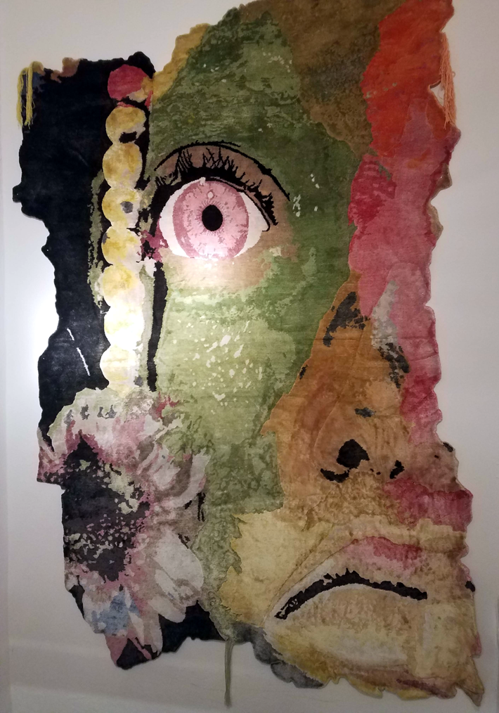 handmade rug art depicting a stylized face by ashley bickerton for henzel studio on display at rossana orlandi during milan design week 2019