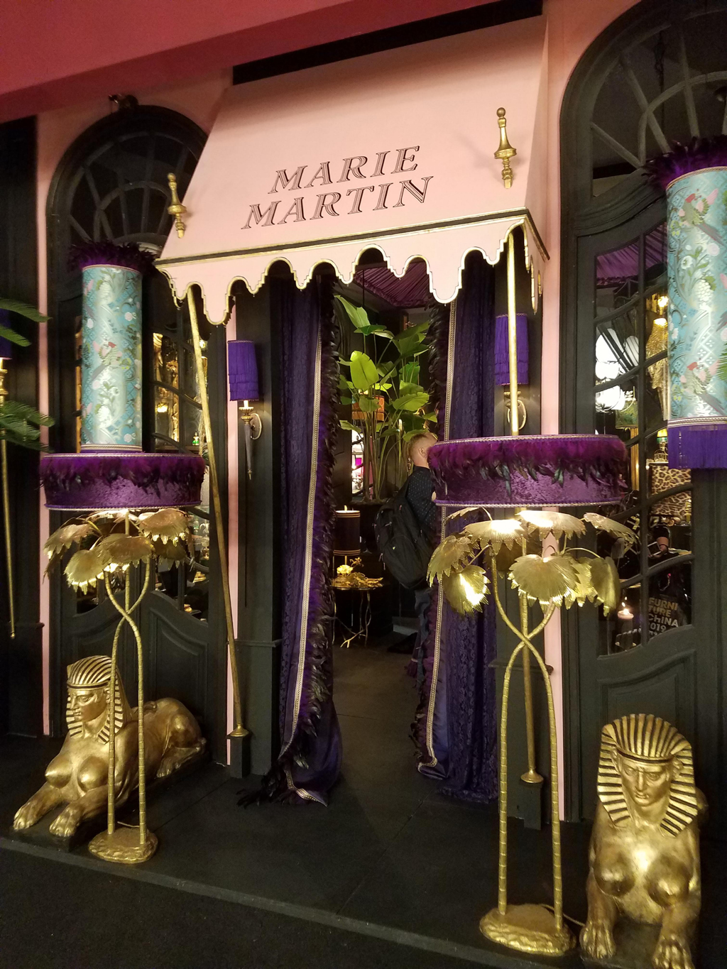 marie martin stand at euroluce 2019 with two tropical inspired purple and gold chandeliers and a pink awning outfront