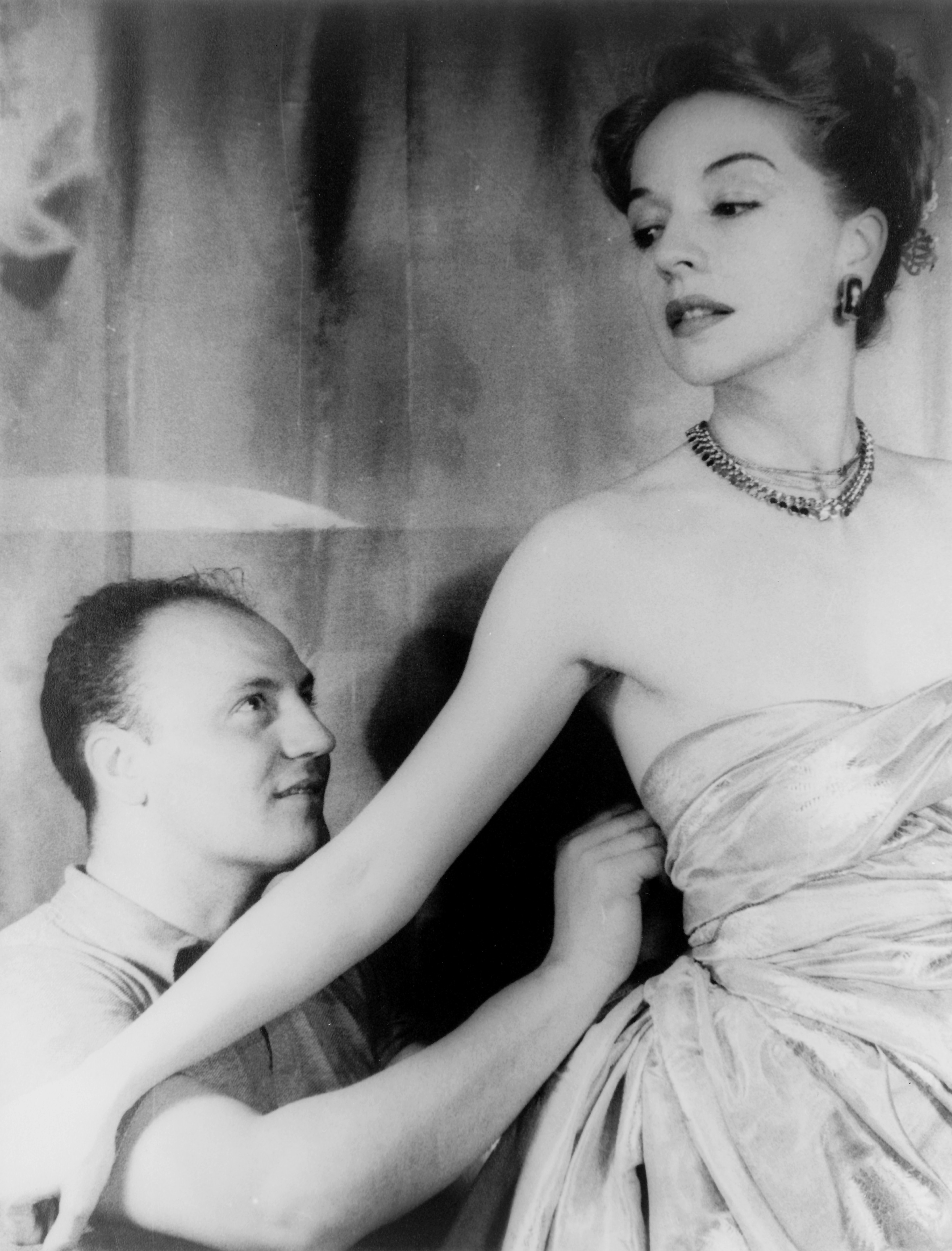 Fashion designer Pierre Balmain fitting haute couture gown on actress Ruth Ford, 1947 - Balmain Paris