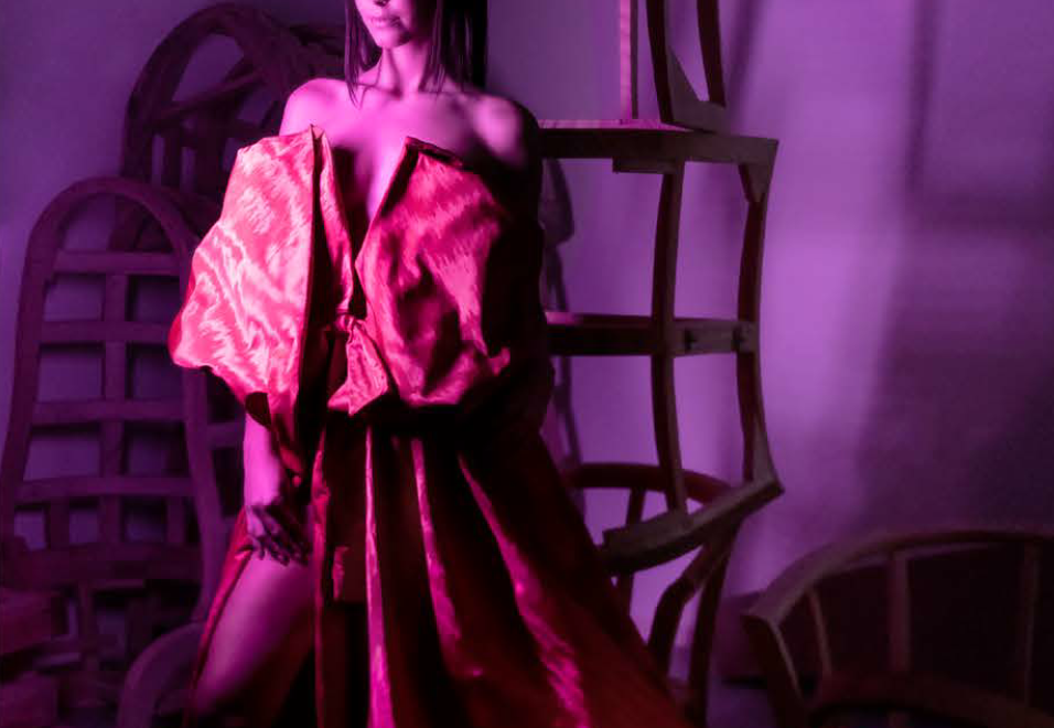 A beautiful model posing with furniture in a red dress - The Haute Craftsmanship Edit by KOKET