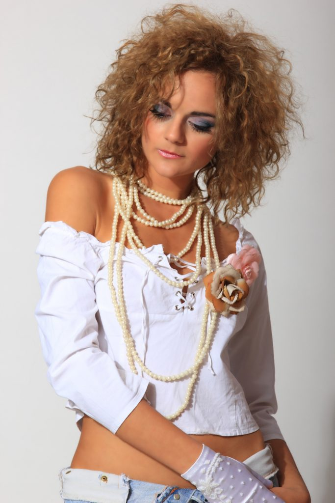 woman wearing large pearls around her neck with rose pins (a summer 2019 trend) on her white blouse.