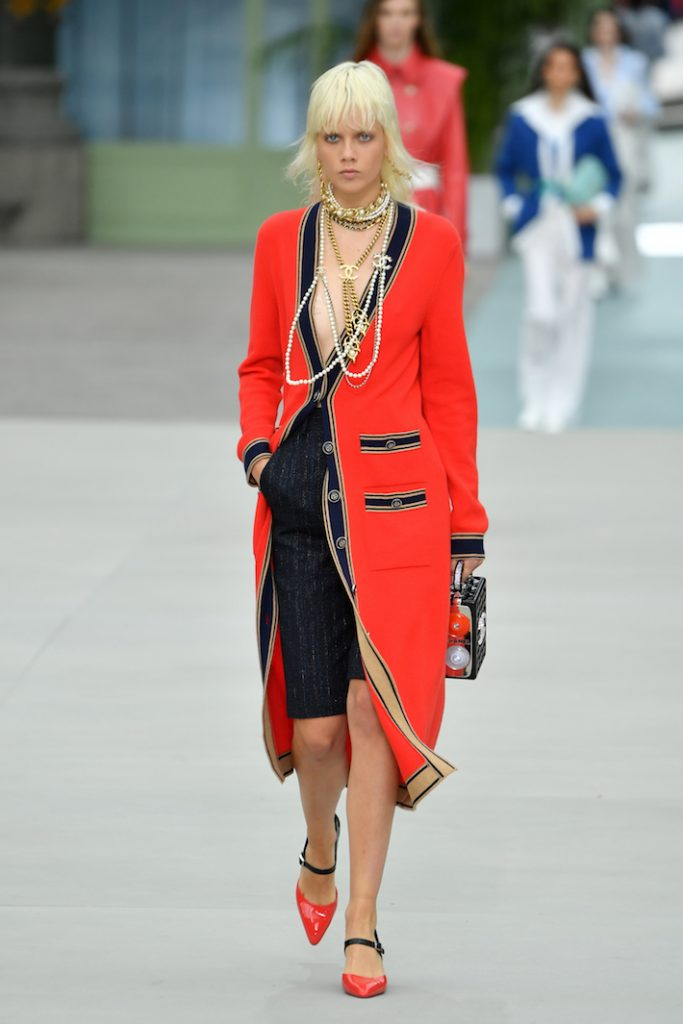 A model walks the runway during Chanel Cruise 2020 Collection wearing a red longline blazer and logo neck beads.