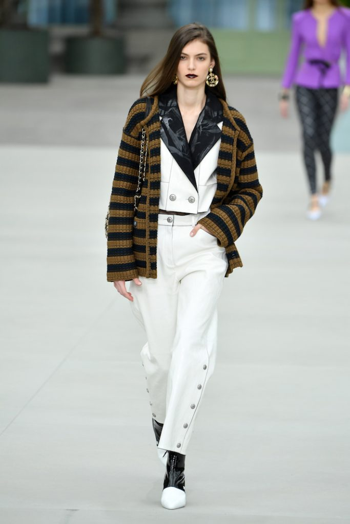 A model walks the runway during Chanel Cruise 2020 Collection wearing matching pant suit and striped sweater
