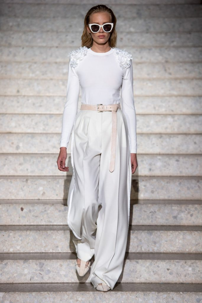 A model walks the runway during the Max Mara Resort 2020 Fashion Show wearing a white blouse and cream colored Palazzo pants