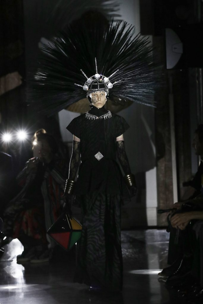 A model walks the runway at the Gucci Cruise 2020 wearing a dramatic black headwear
