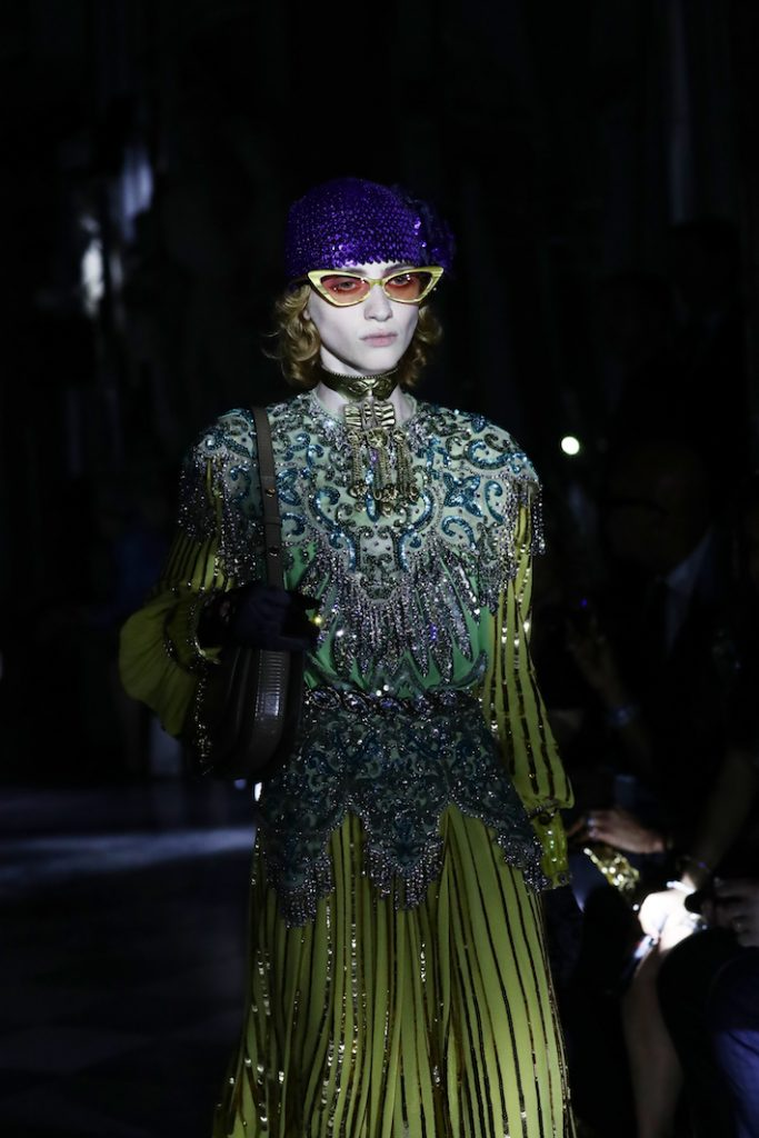 A model walks the runway at the Gucci Cruise 2020 wearing a cool toned embroidered and beaded chest piece.