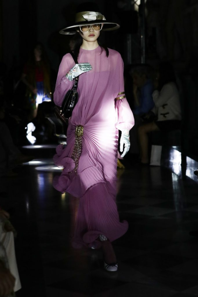 A model walks the runway at the Guccu Cruise 2020 wearing a light purple gown with gold accents