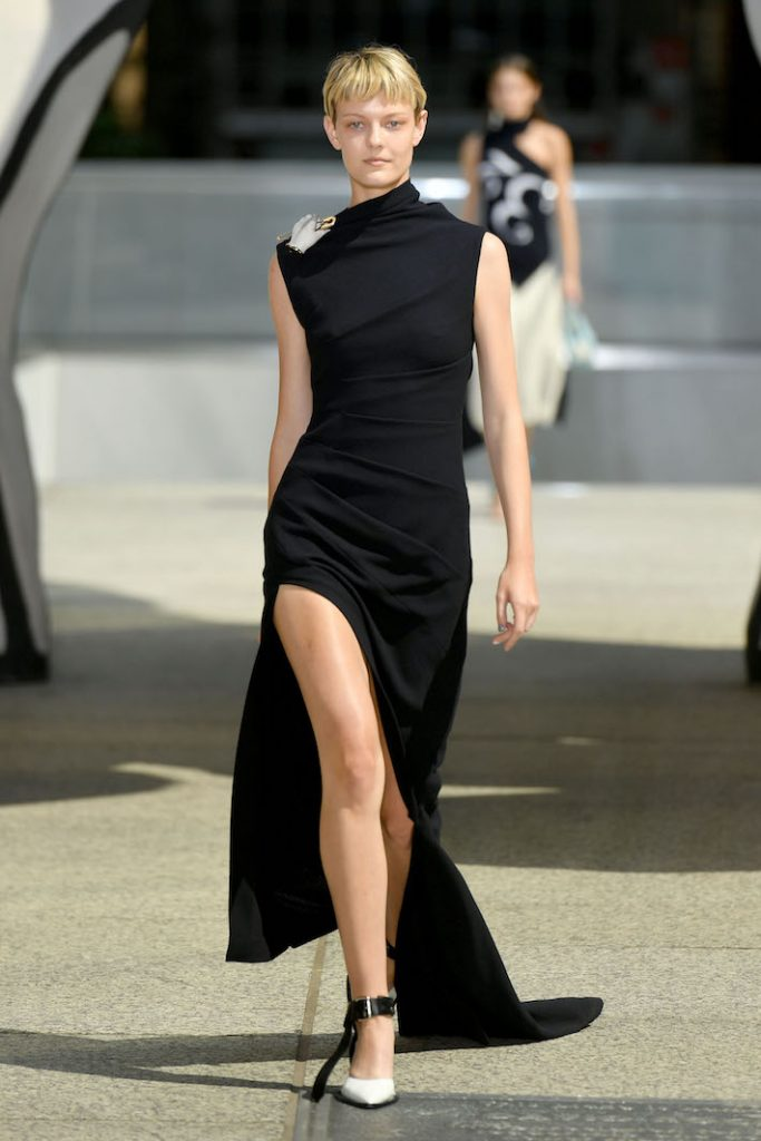 A model walks the runway during the Monse Resort 2020 Fashion Show wearing an all black asymmetric gown