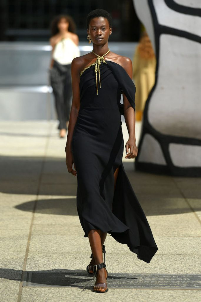 A model walks the runway during the Monse Resort 2020 Fashion Show wearing a black halter gown with gold detailing at the top