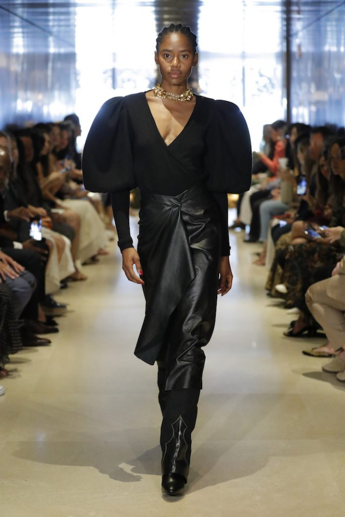 A model walks the runway during Johanna Ortiz Resort '20 Collection show wearing a black blouse with puffed out sleeves and a long black leather skirt