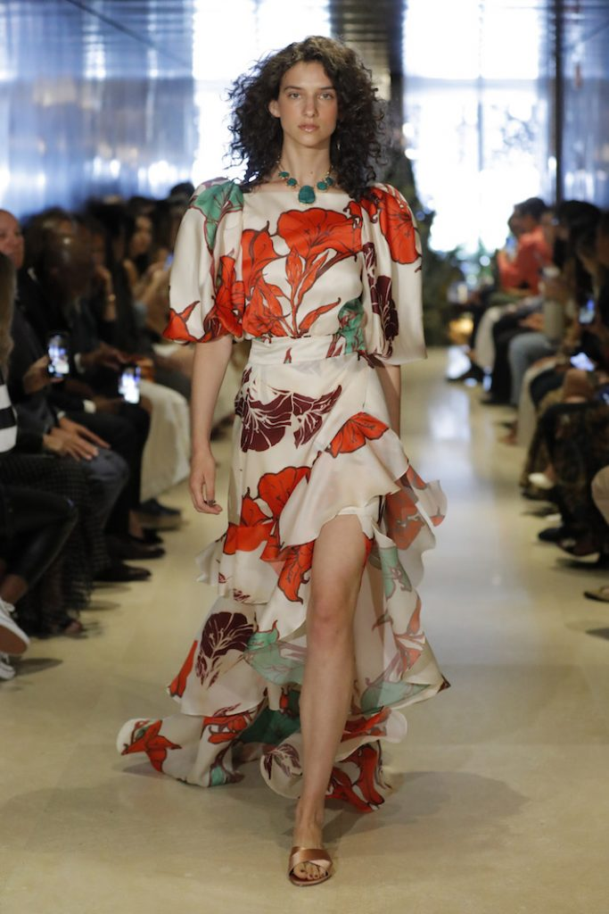 A model walks the runway during Johanna Ortiz Resort '20 Collection wearing a floral printed high-low maxi dress
