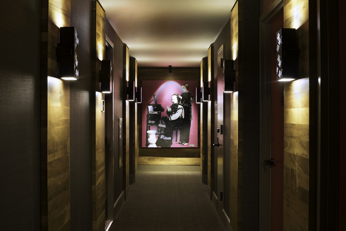 Dim lit hallway leading to guest rooms
