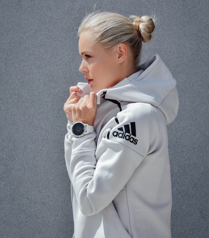 a woman wearing an Adidas Jacket showing how to wear the athleisure trend