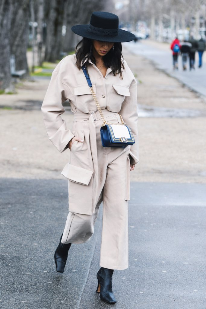 woman wearing a beige stylish one piece suit (a summer 2019 trend), with large pockets.