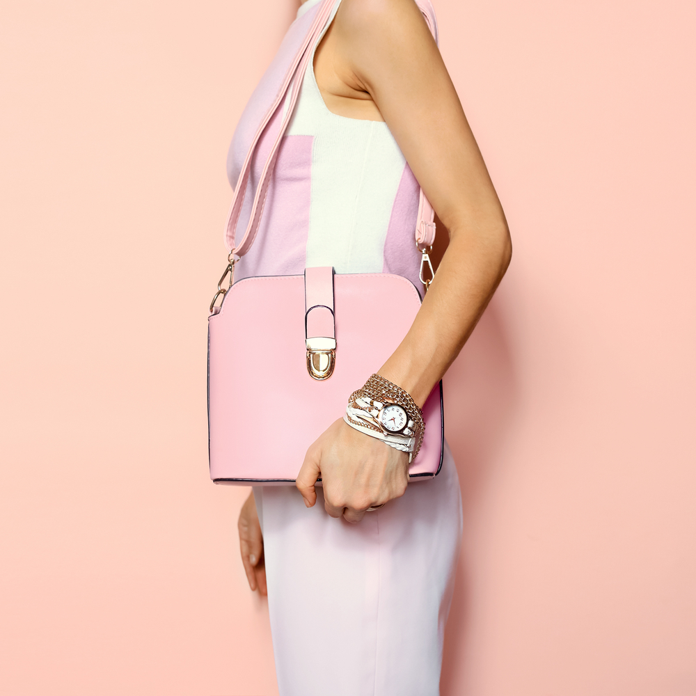 side view of woman wearing purple pastel dress ( a summer 2019 trend), and a light pink handbag