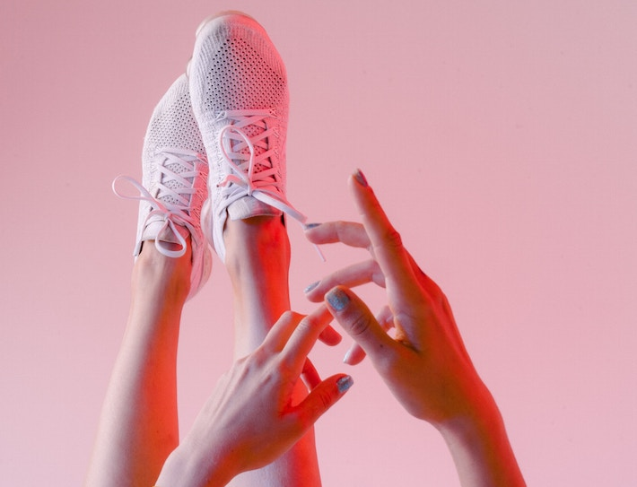 a womans legs and hands with pink sneakers showing how to wear the athleisure trend