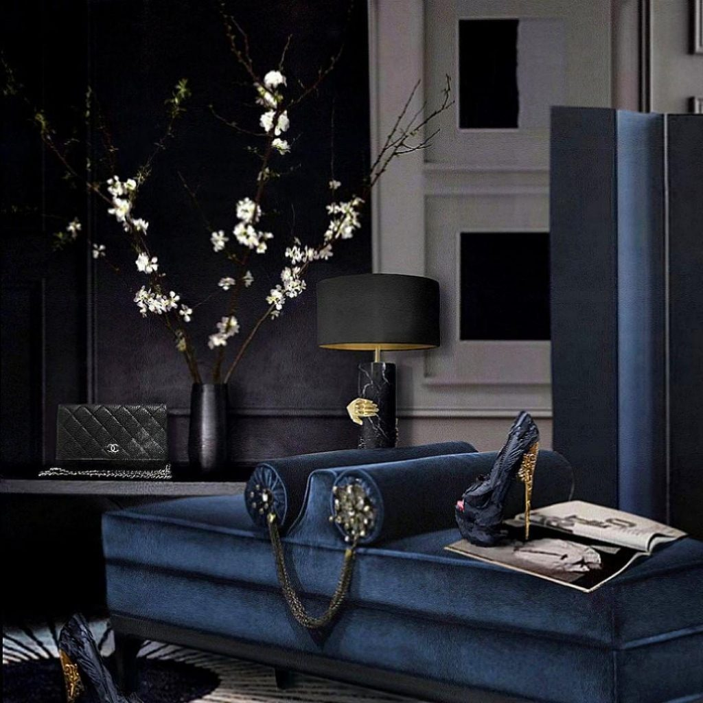 Dark colored sitting room with royal blue details featuring KOKET Vengeance Table Lamp and lele bench for the new dark woman
