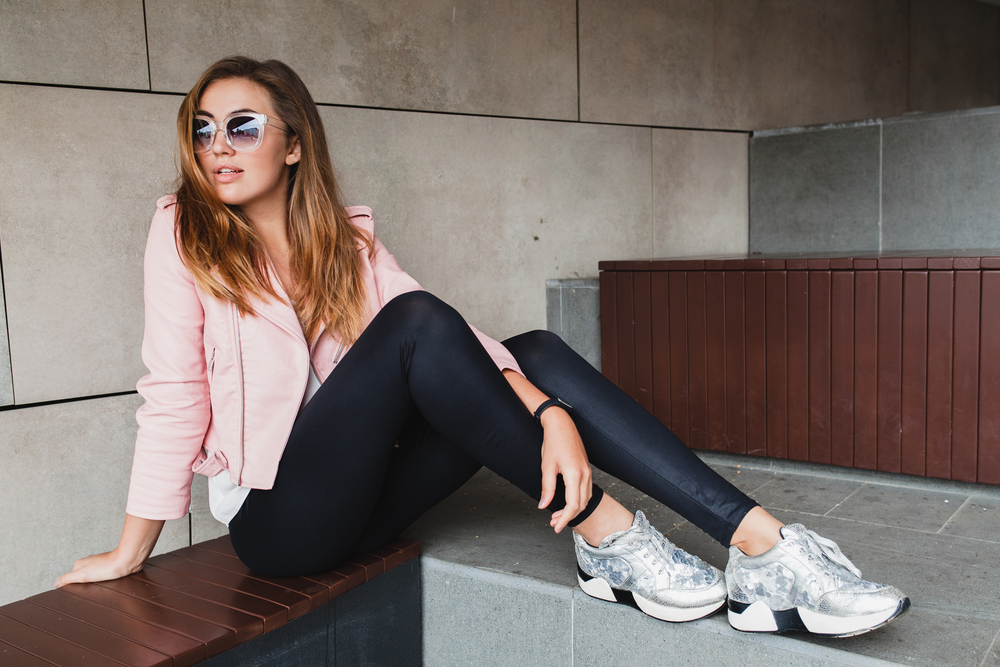 young woman wearing a pink leather jackets and silver fashion sneakers (summer 2019 trend).