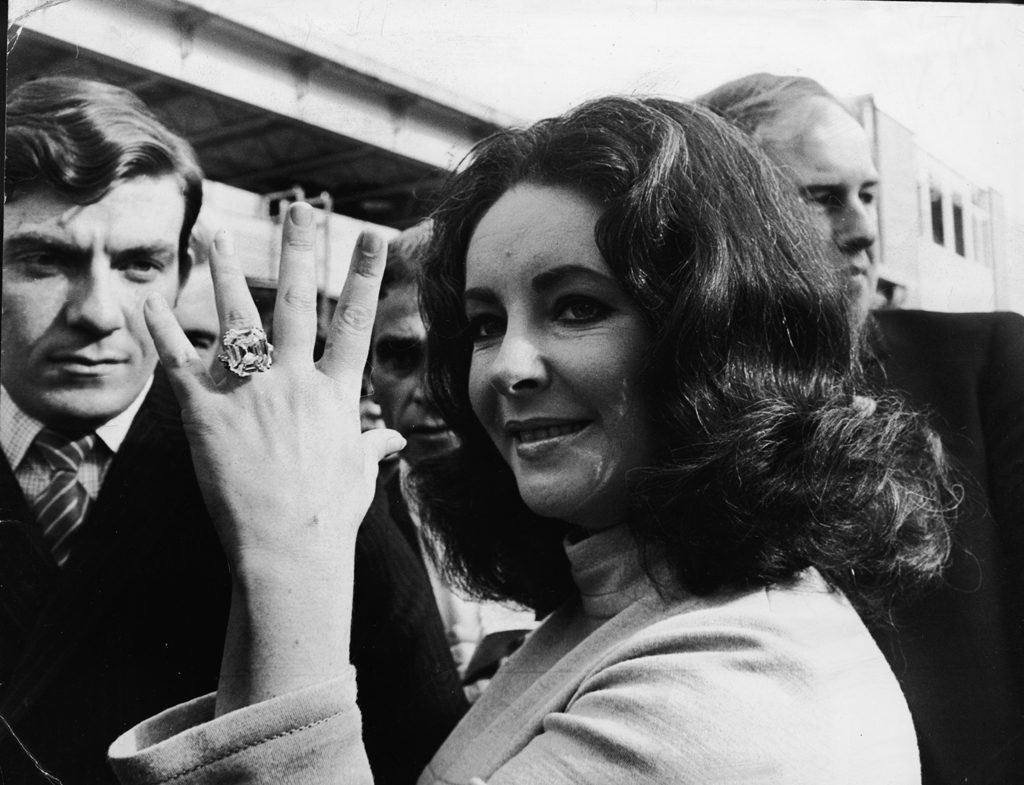 elizabeth taylor showing off her celebrity engagement ring from husband richard burton