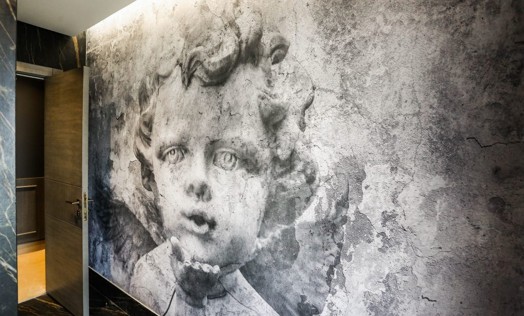 large classical black and white mural of a young boy in the powder room in an amman based interior design project by maysoon haymoor
