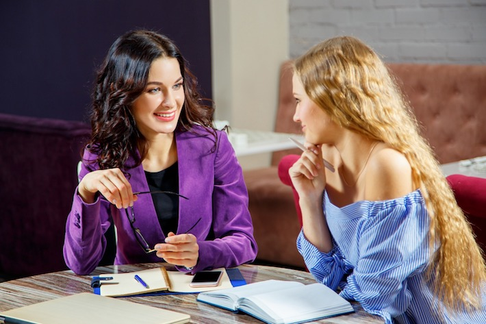 Two woman discussing business inquires -Meet Alli McCartney & UBS Alignment Partners