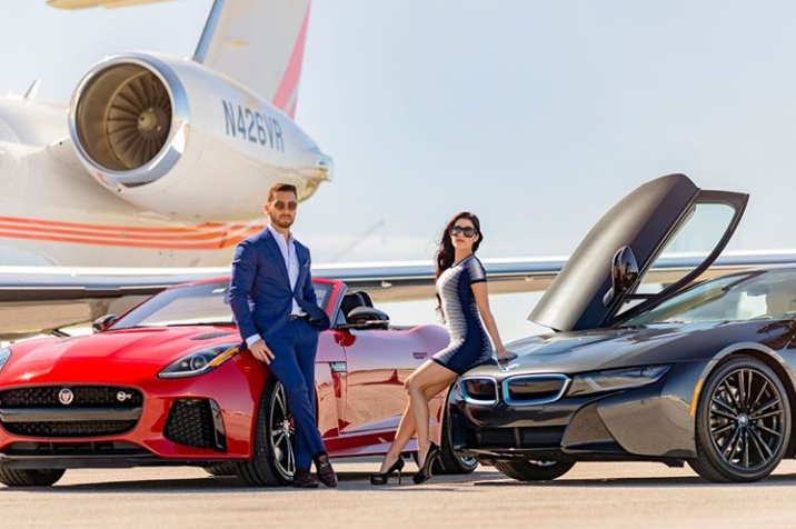 man and woman standing by luxury cars from revolve car subscription service