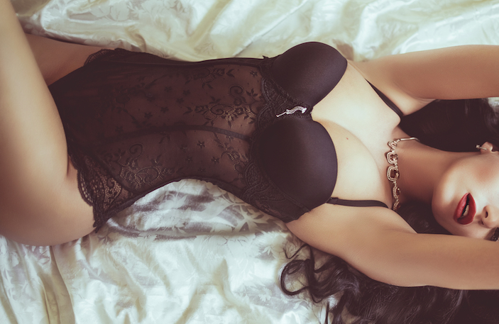 woman laying on bed wearing lingerie