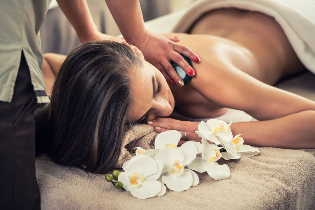 Young woman enjoying the therapeutic effects of a traditional hot stone massage at luxury spa and wellness center - luxurious gifts for every occasion