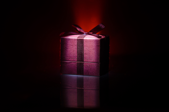 red gift box with red bow on dark toned background - luxurious gifts for every occasion
