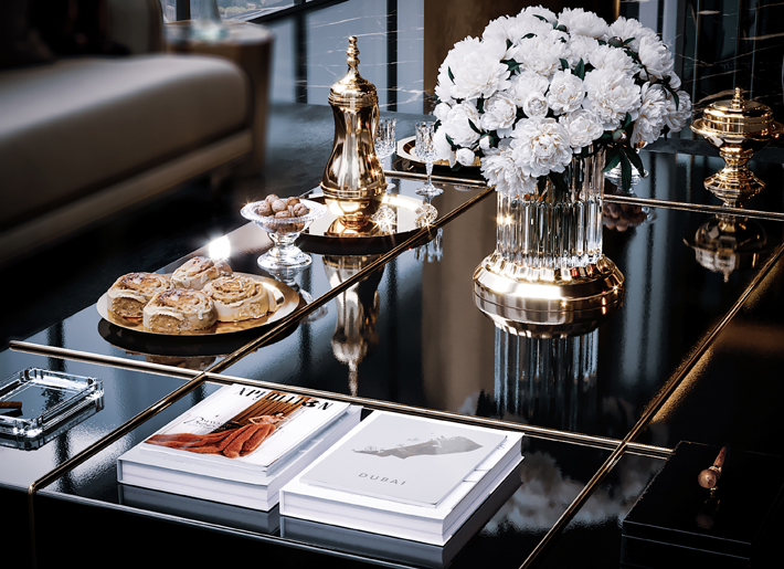 detail of accessories on a mirror coffee table in a luxury interior by celia sawyer