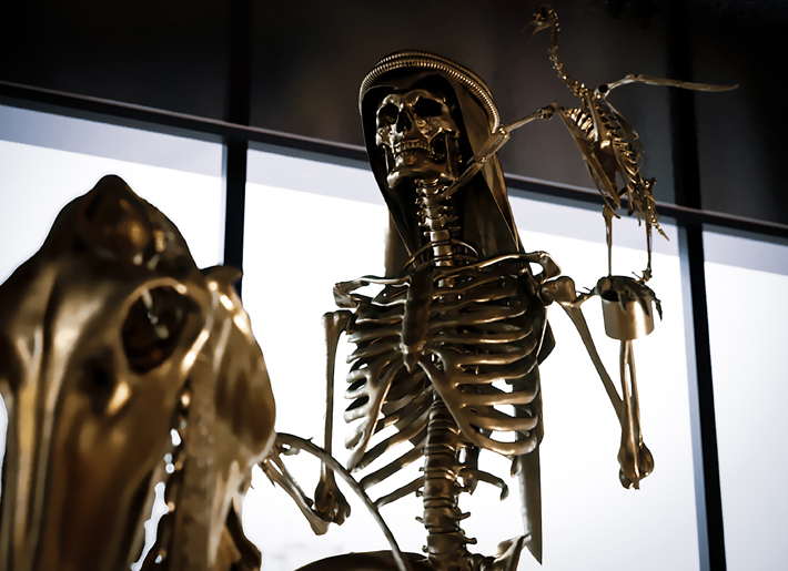 24k gold skeleton statue of an arabian man on a horse with a bird of prey on his shoulder by stephen cawston