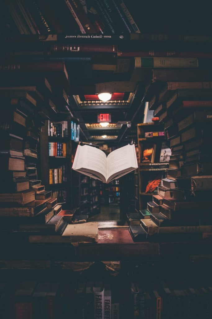 books stacked in a library - ways to develop a winning mindset