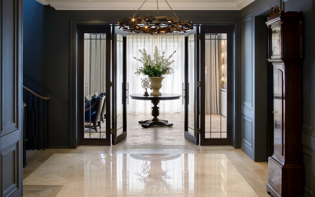 foyer design with dark walls, grandfather clock and marble floors
