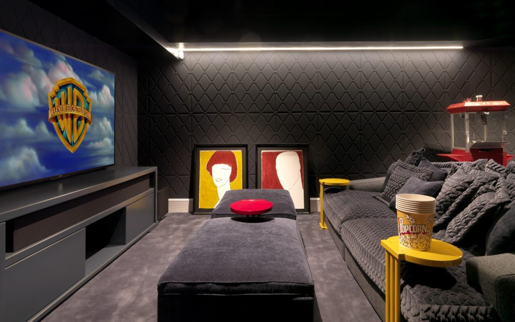 contemporary in-home movie theater in london with gray quilted walls and upholstery and red and yellow accents