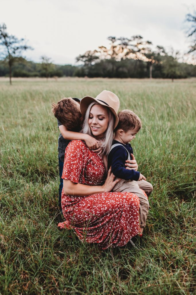 hot nanny hugging two kids in a field