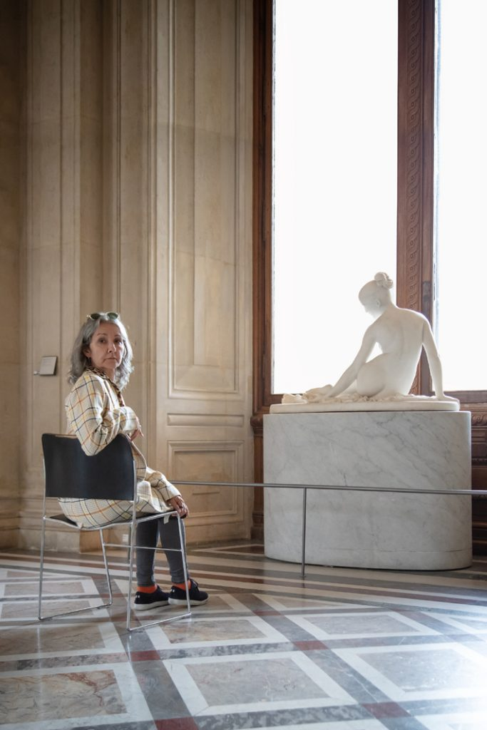 Annick Ménardo at the Louvre next to the sculpture that inspired her fragrance, Lorenzo Bartolini's Nymphe au Scorpio, 1835