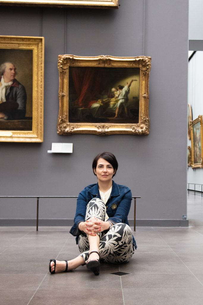Delphine Lebeau in front of the painting that inspired her fragrance, Jean-Honoré Fragonard's Le Verrou.