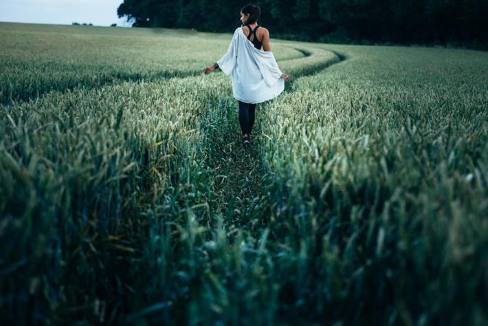 Woman walking in a field, Photo by Clem Onojeghuo Unsplash