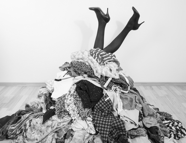 woman's legs wearing heels sticking out of a pile of laundry - power of decluttering