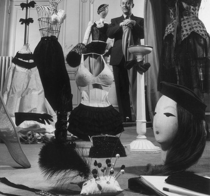 history of fashion - Circa 1955: French fashion designer Christian Dior (1905 – 1957) standing in a showroom with samples of his design accessories for women, including hats, hat pins, gloves, muffs, lingerie, hosiery, evening bags, and jewelry. Photo by Hulton Archive/Getty Images