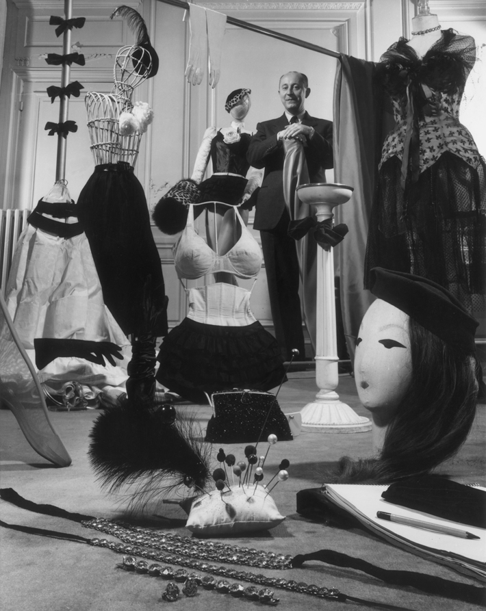Famous fashion designer Christian Dior (1905 - 1957) standing in a showroom with samples of his design accessories for women, including hats, hat pins, gloves, muffs, lingerie, hosiery, evening bags, and jewelry